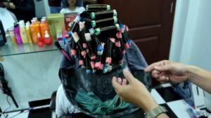 Cận cảnh việc dùng ống nhựa định hình tóc trước khi phủ thuốc uốn dùng cho phương pháp uốn lạnh.